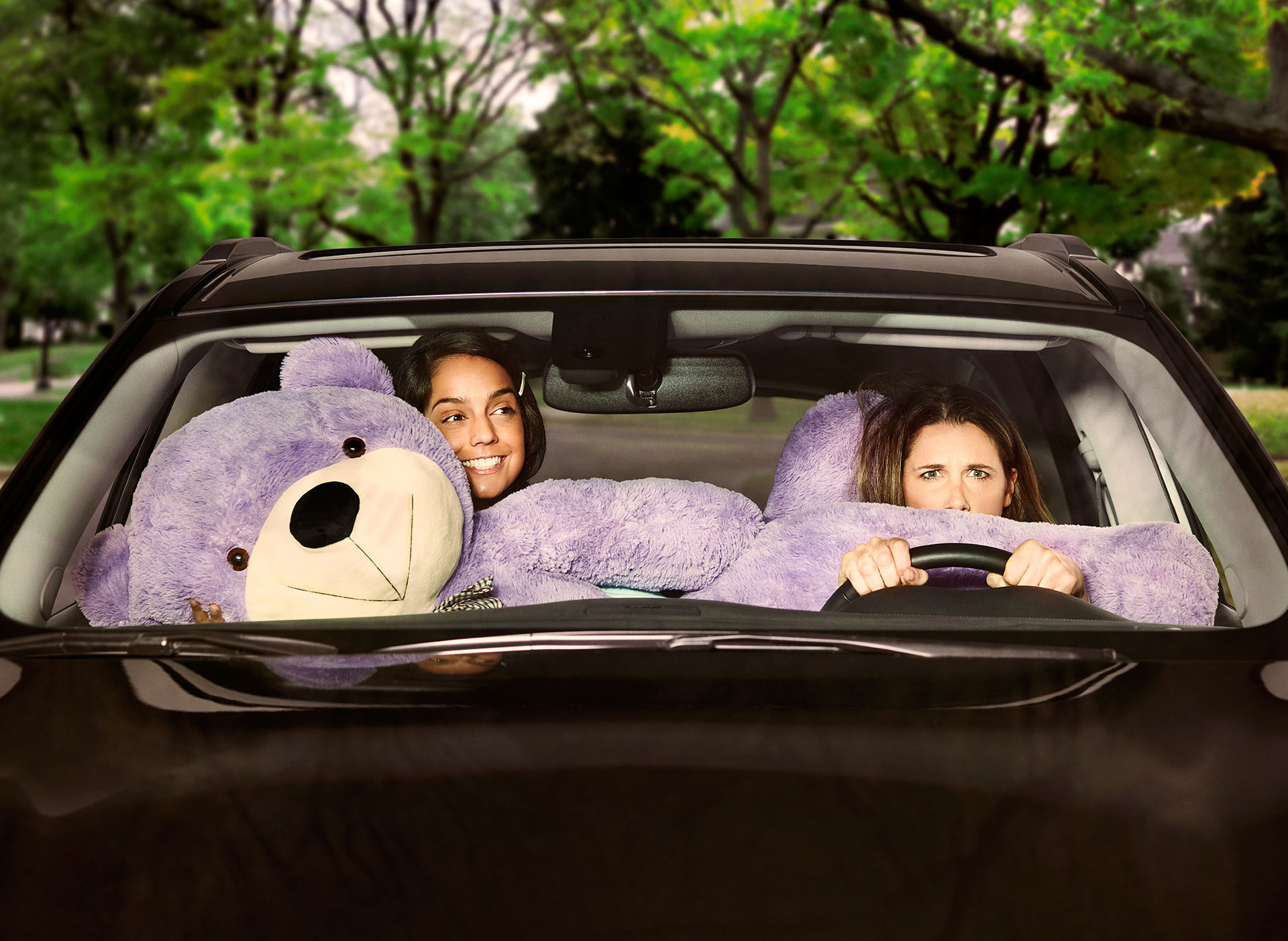 two girls in car with giant purple teddy bear taking up all the space and annoying the driver by Jocelyn for Netlift