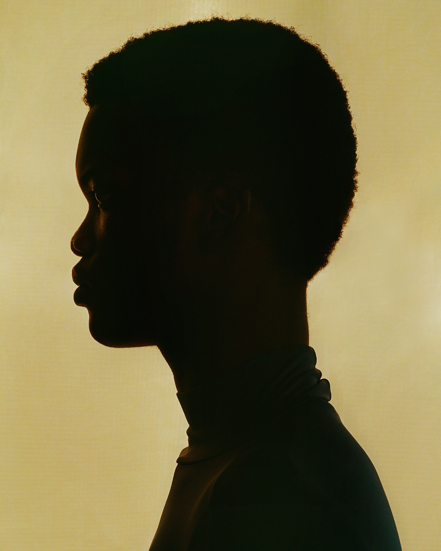 profile silhouette of black female model on light yellow background photographed by Oumayma B Tanfous for Moncler as a story for Document Journal magazine
