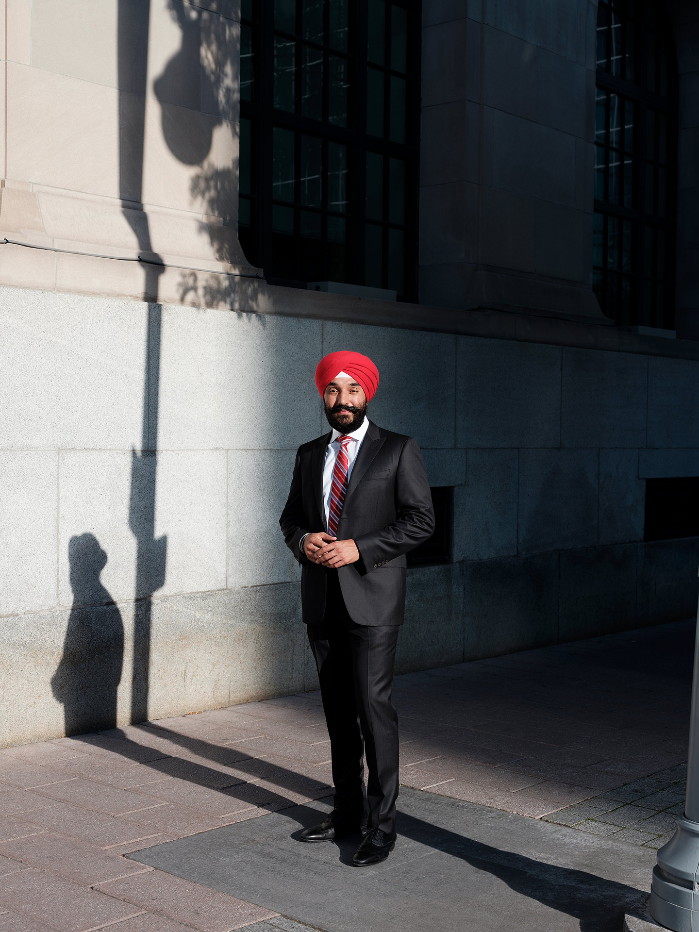 CPA Navdeep Bains in suit smiling wearing red turban in the street by Guillaume Simoneau for Pivot Magazine