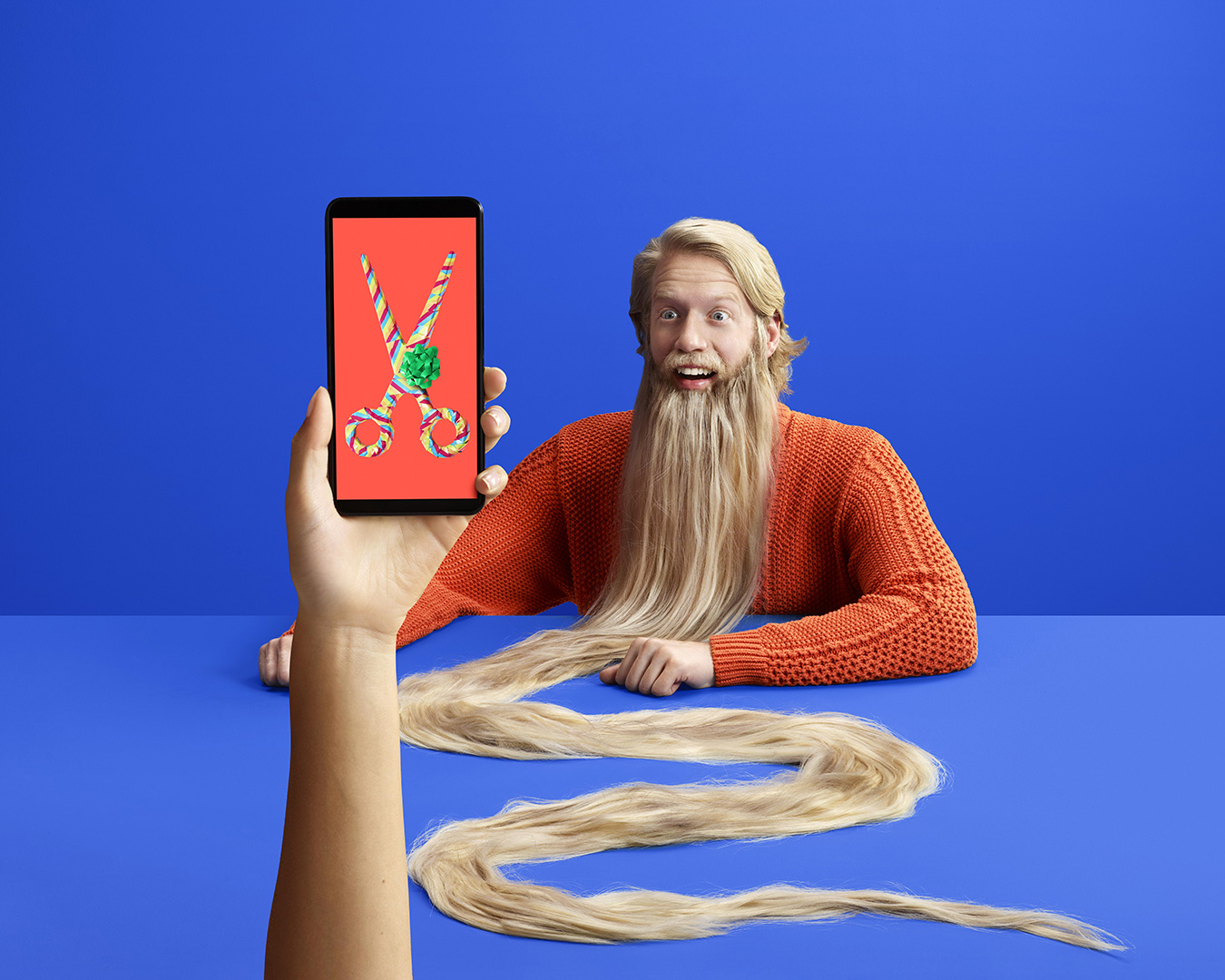 surrealist shot of a man with a very long beard and a hand holding a mobile phone displaying scissors by Simon Duhamel for FIzz