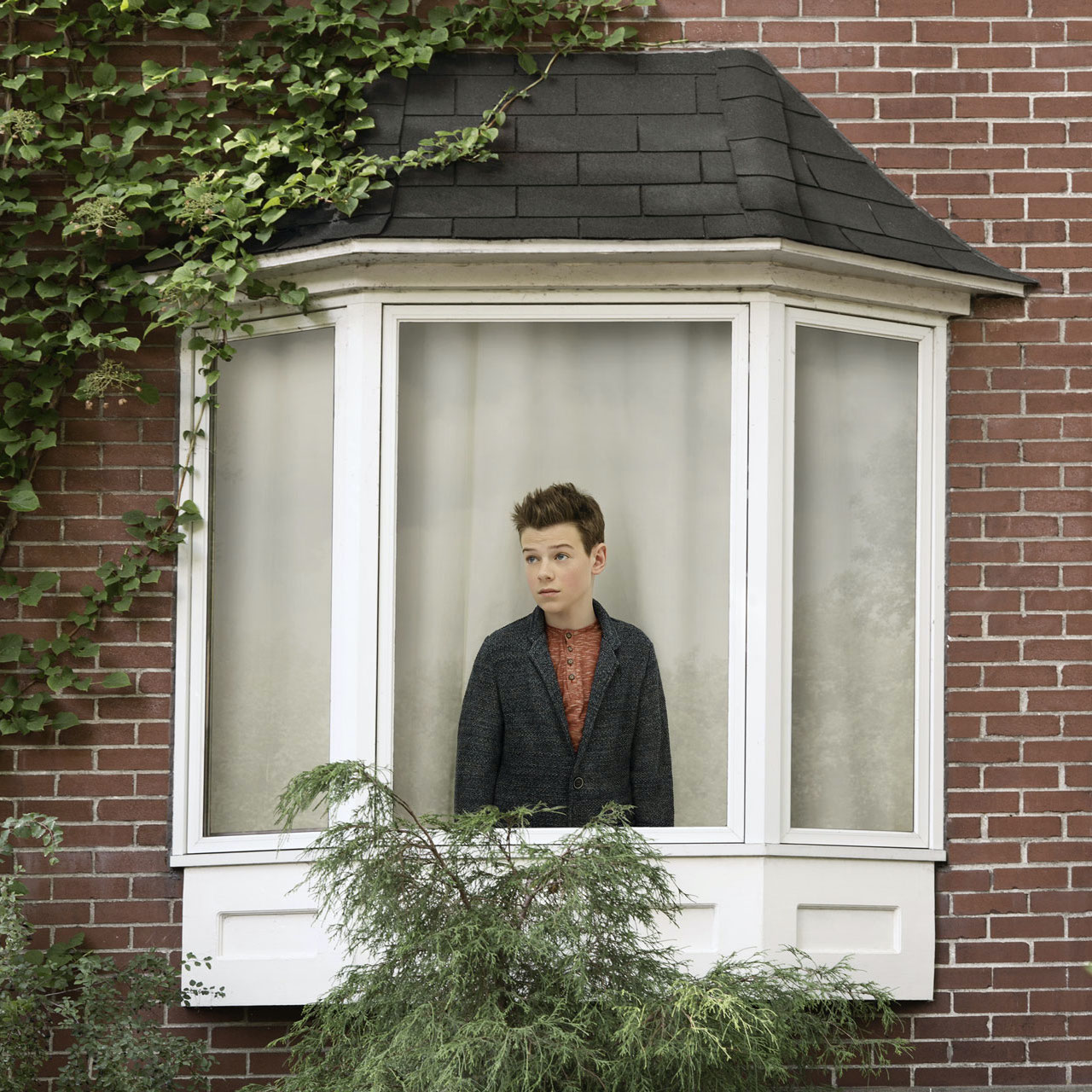 young boy inside house looking out the window by Simon Duhamel for In Between