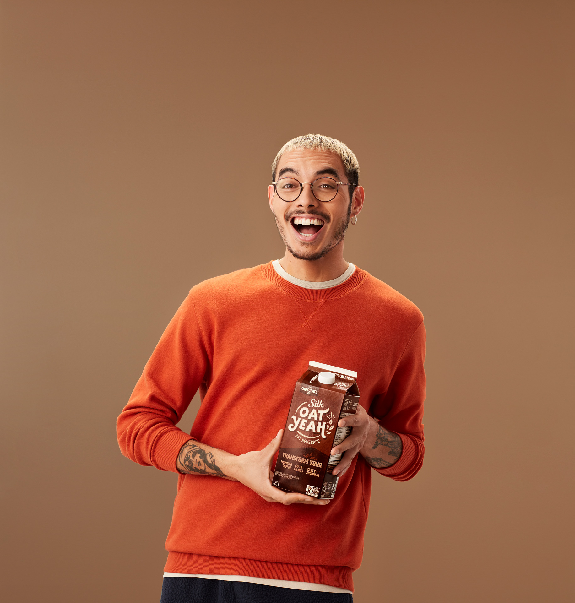 man smiling blonde hair glasses orange sweater holding carton of chocolate oat milk by Simon Duhamel for Oat Yeah Silk and Carl agency