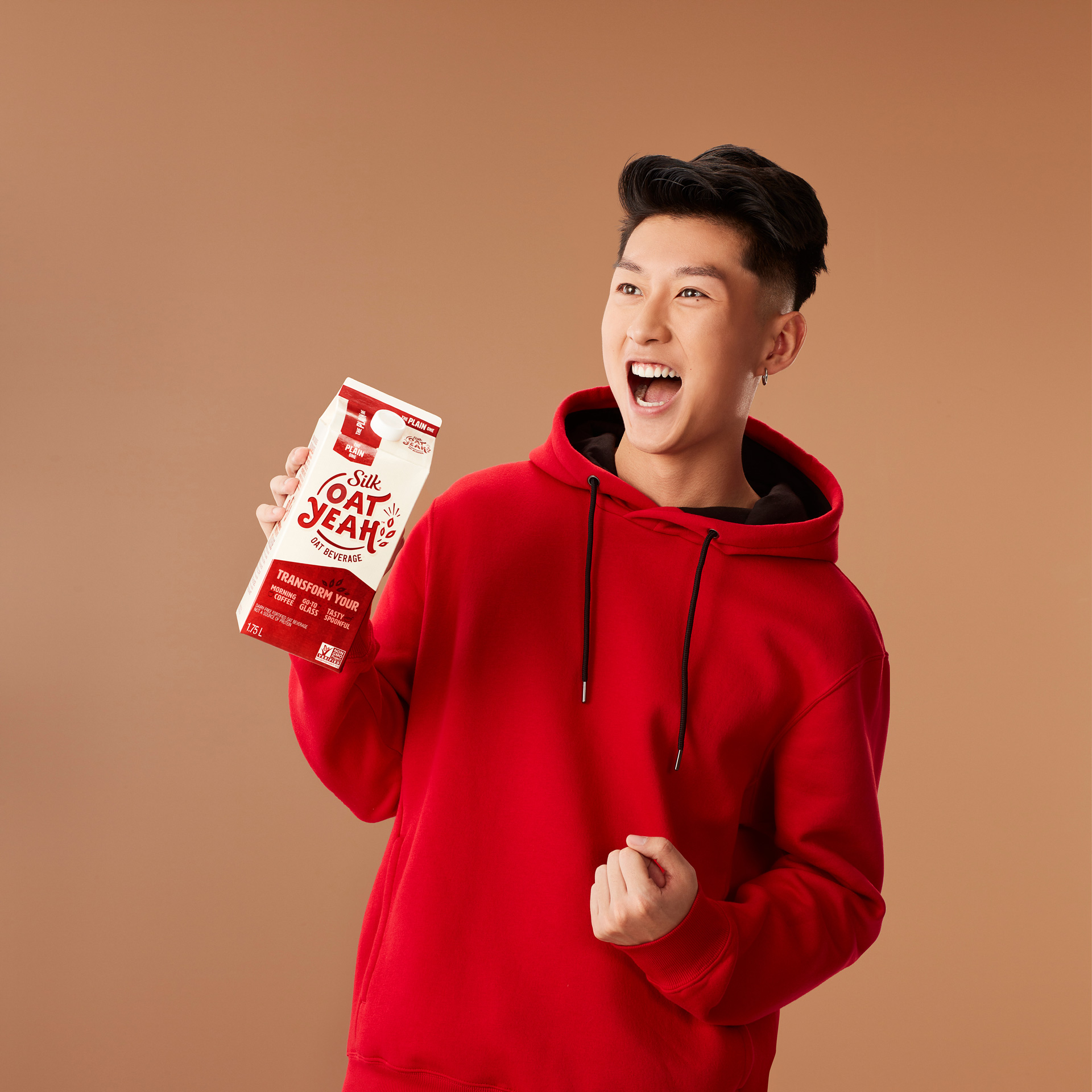 chinese man mouthing yeah holding oat milk carton wearing bright red hoodie by Simon Duhamel for Oat Yeah Silk and Carl agency