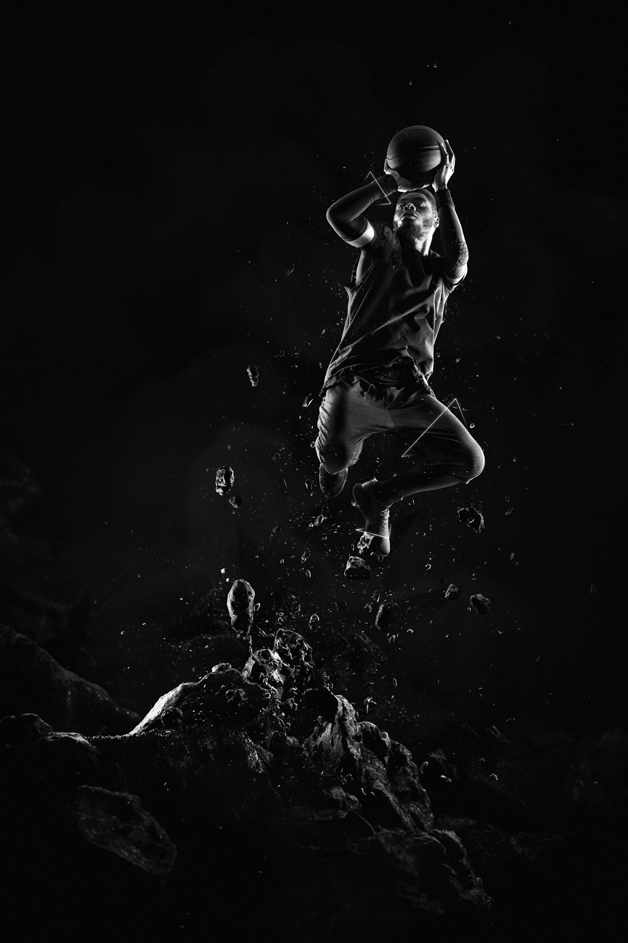 black man posing as basketball player jumping from the ground with debris around basket ball in hand trying to shoot low lighting black and white by Simon Duhamel for W-Hoop