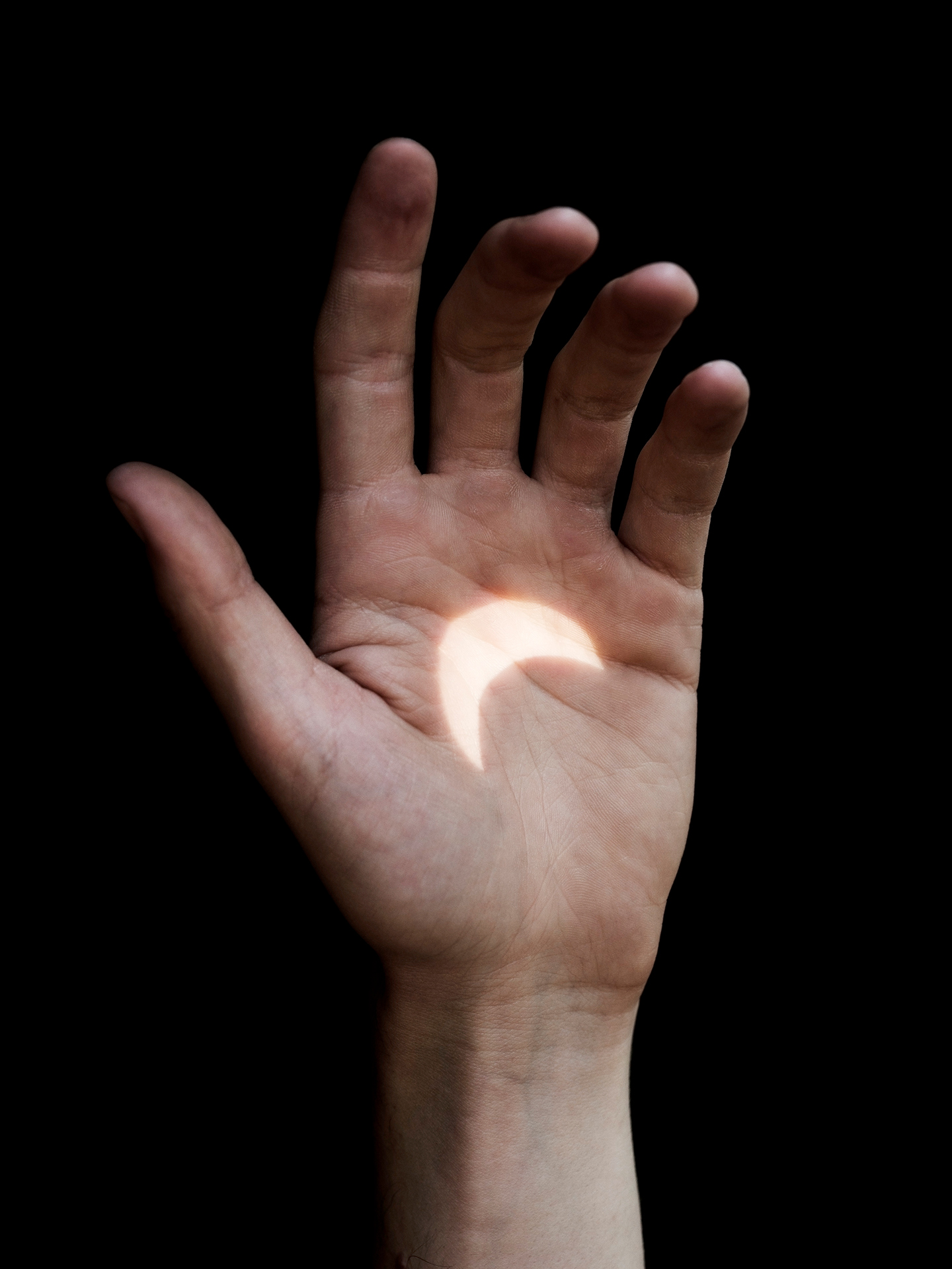 hand surrounded by darkness with moon crescent in light in the palm by Guillaume Simoneau for Solar Eclipse