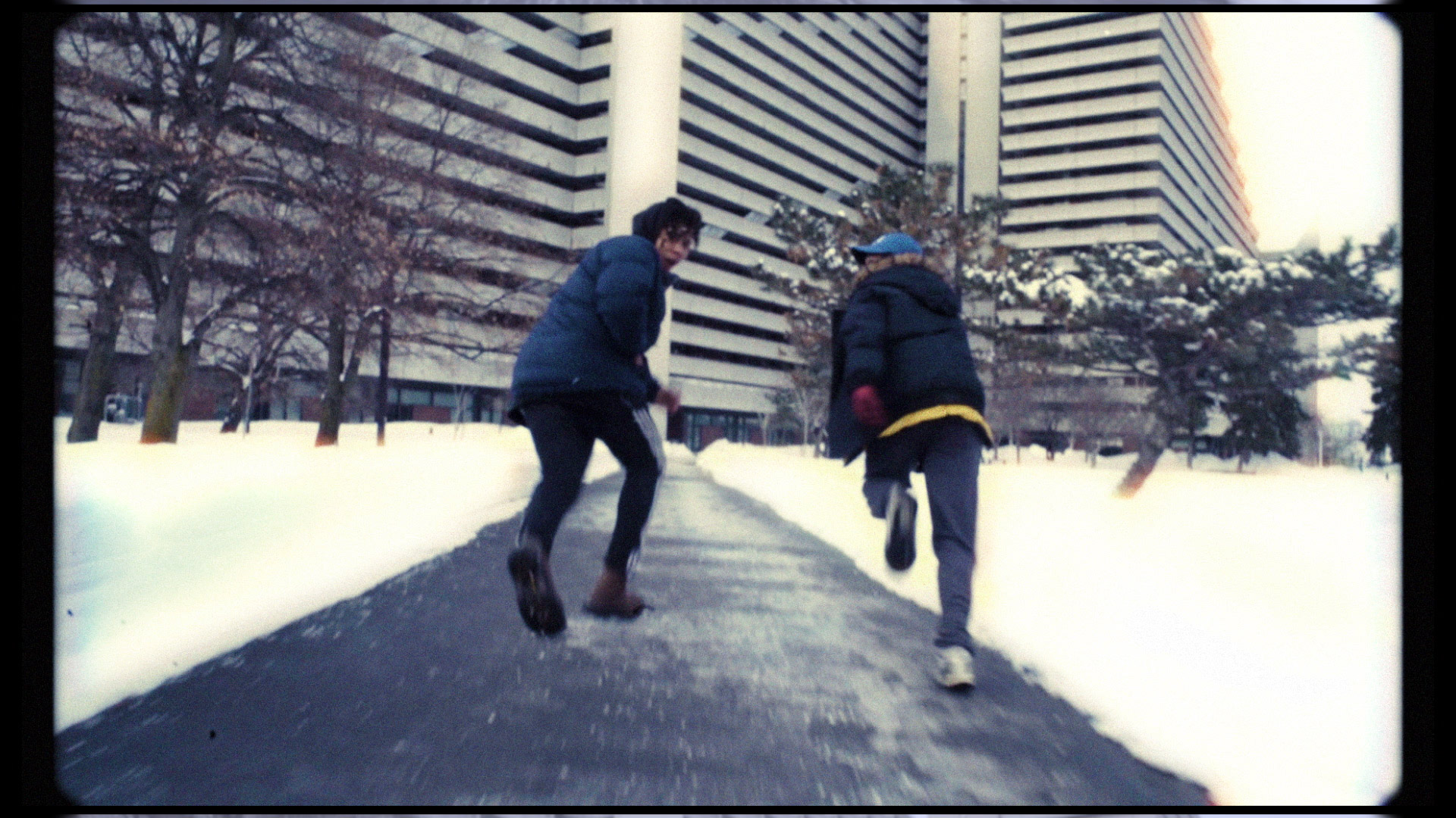 rapper Zach Zoya and friend running on pathway in middle of garden covered in snow in music video Who Dat filmed by Les Gamins