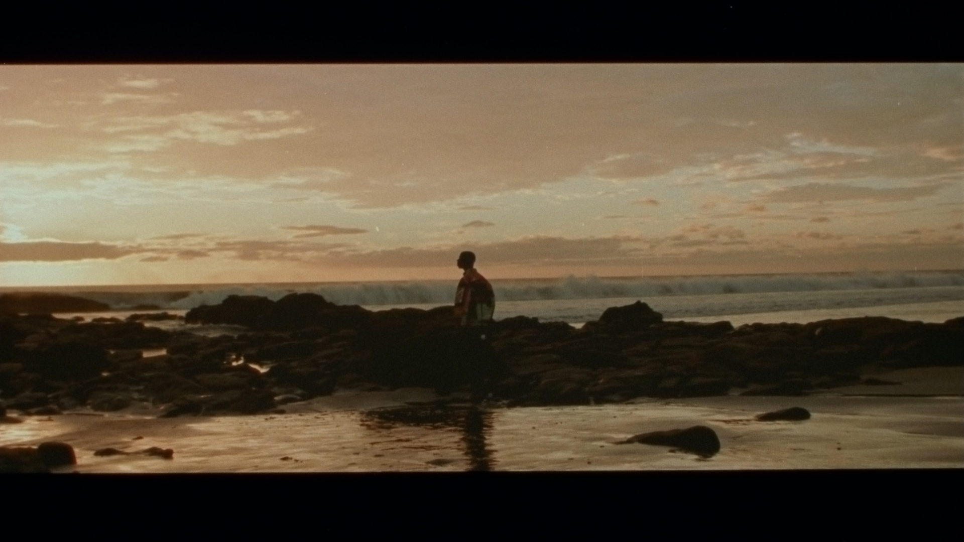 singer Karim Ouellet next to the sea at sunset for his music video of La Mer A Boire filmed by Les Gamins