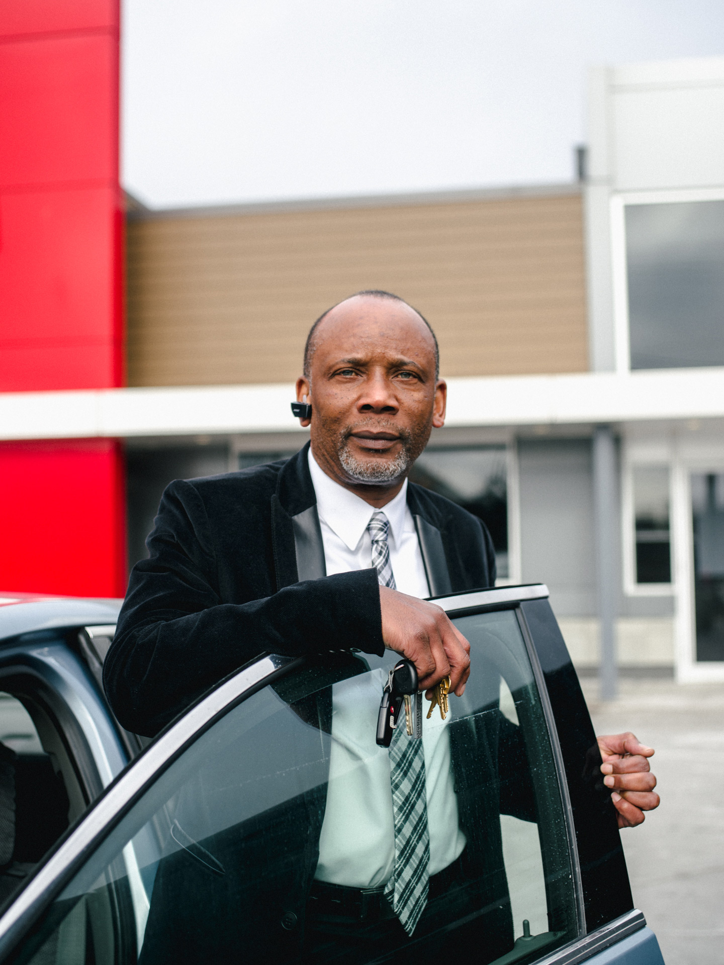middle aged black man with blue eyes and an earpiece looking at camera while getting in his car by Alexi Hobbs for McDonald's with N / A agency