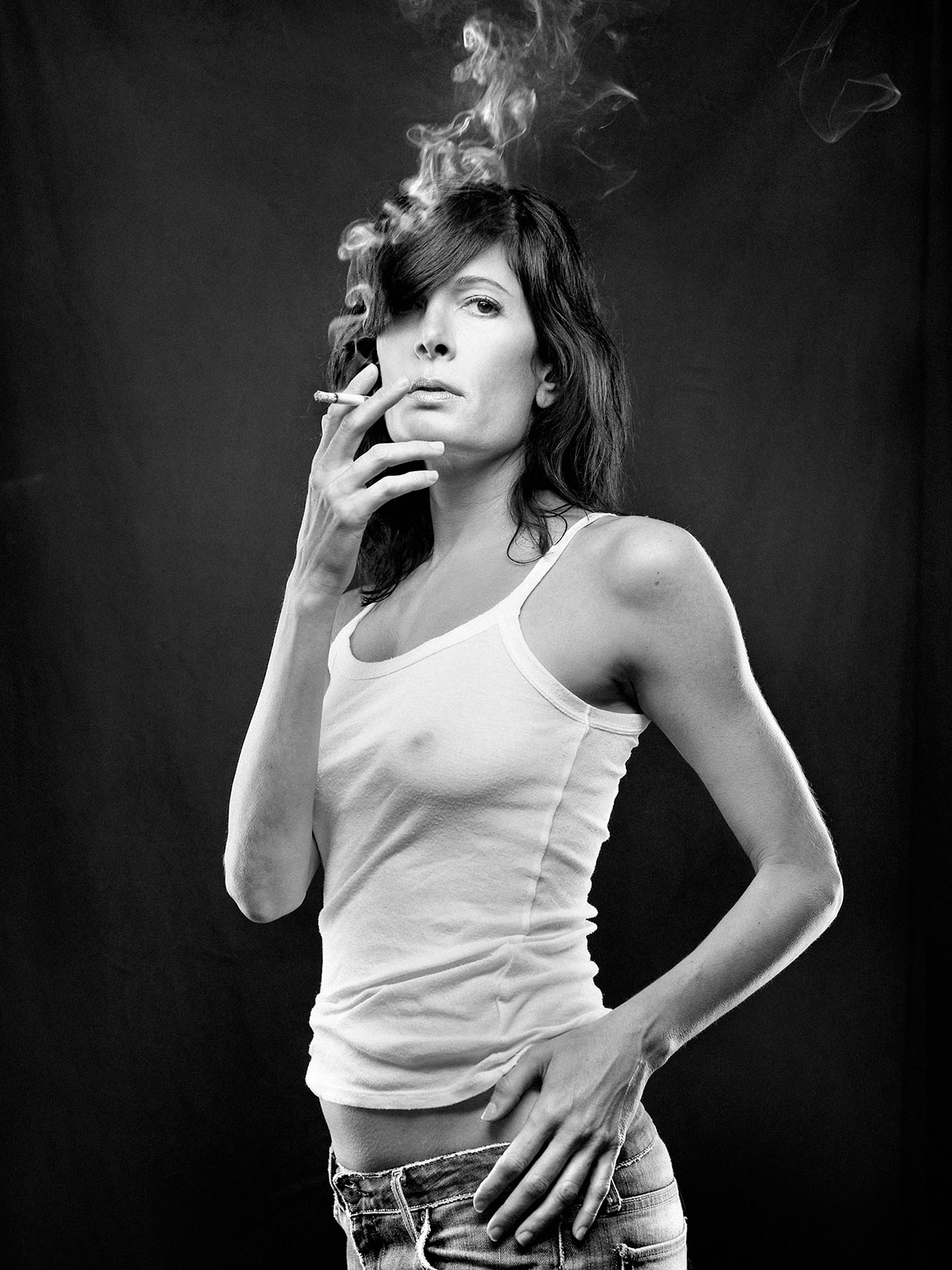 portrait of Anne-Marie Cadieux in black and white wearing white short tank top and low jeans smoking a cigarette on black fabric background by Jocelyn Michel for Voir