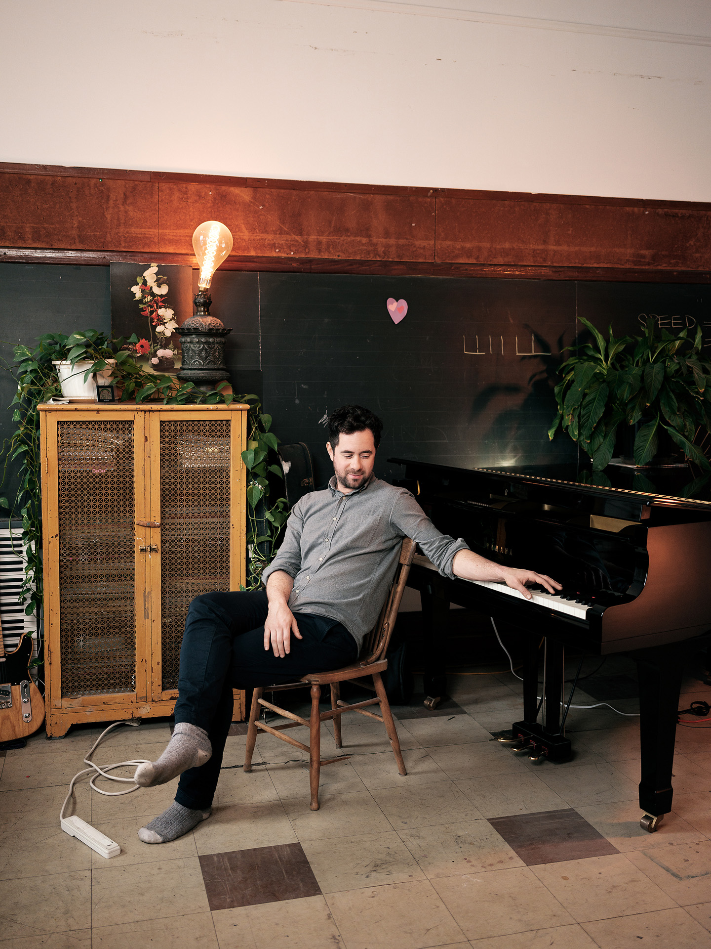 singer Jean-Michel Blais sitting on wooden chair in front of piano one hand on the keys wearing grey shirt black pants socks and no shoes photographed by Guillaume Simoneau for Voir's magazine cover