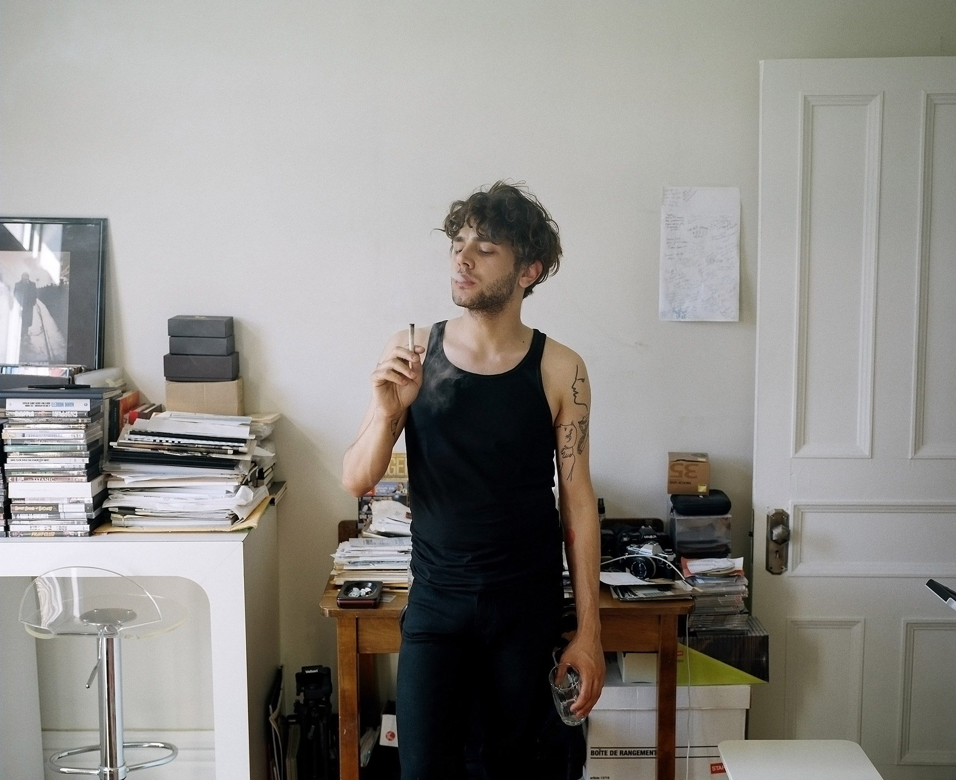 portrait of cinema director and actor Xavier Dolan smoking a cigarette in his office dressed in casual black clothes by Guillaume Simoneau for The Walrus